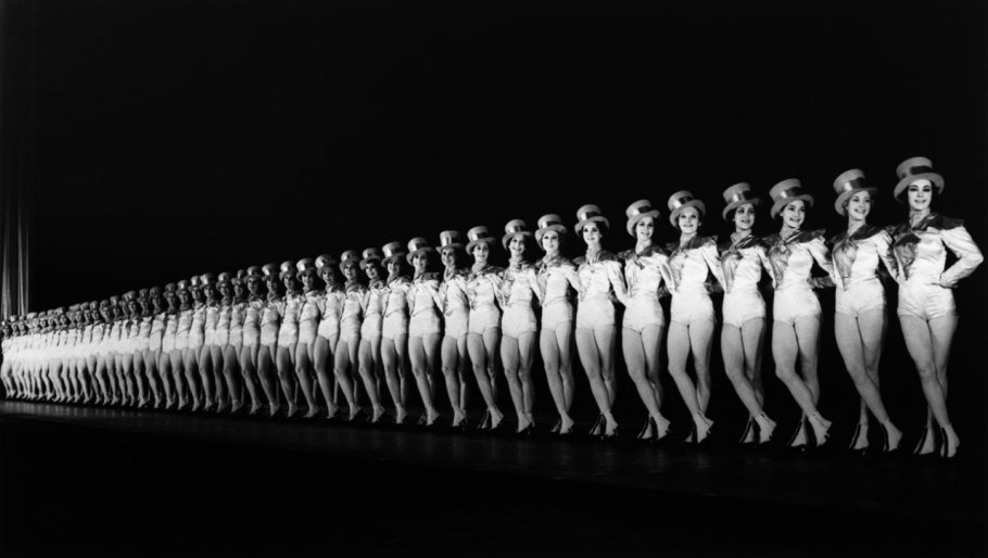 02 Onstage in 1937, the Rockettes cut a sharp, diagonally receding line—in white and top hats—against the dark backdrop